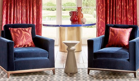 Dark blue velvet matching chair with red cushions in lounge